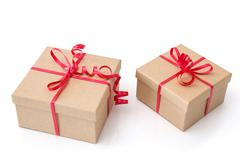 Two gift boxes with red ribbons on white background Stock Photos