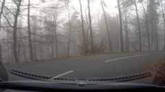 Vehicle shot in mist, descending in hairpin turn in the Veluwe moraine hills Stock Footage