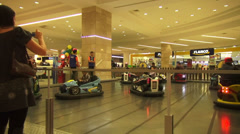 Playing area in a shopping mall, amusement, bumper cars, kids, parents, fun Stock Footage