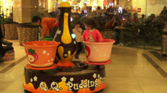 Playing area in a shopping mall, pudding cups spinning around, kids, fun Stock Footage
