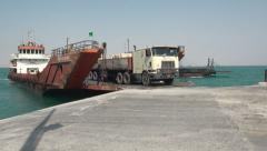 Heavily loaded truck drives off ferry in Iran Stock Footage