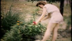 749 - garden work includes care for her flowers - vintage film home movie - stock footage