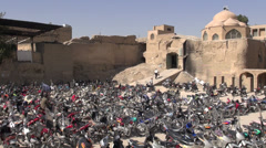Motorbikes parking lot in front of a classic mosque in Isfahan Iran Stock Footage