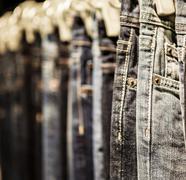 Garment rack with classic jeans close up shot Stock Photos