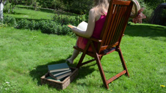 Woman in shorts sit on wooden chair and read study book Stock Footage
