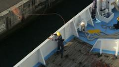 Sailor throws line to shore from bow of ship Stock Footage