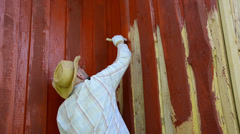 Worker man with glasses paint wood wall with brush in red color Stock Footage