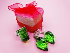 Jewelry ring and earrings with bright gem emerald crystals Stock Photos