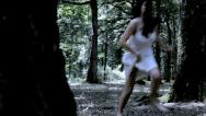 Beautiful woman running scared in forest Stock Footage