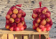 two bags full of delicious red apples standing on a wooden chest at a street - stock photo