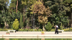 Veiled woman and husband walk through park in Iran Stock Footage