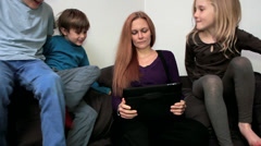 A day in the life of home - Mum and kids on the sofa with the ipad Stock Footage