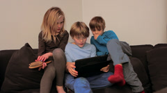 A day in the life of home - Three kids on the sofa on the ipad - stock footage