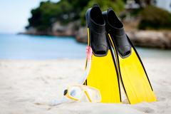 yellow fins and snorkelling mask on beach in summer - stock photo