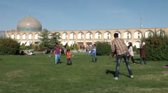 Iranian family playing games in a park with beautiful mosque architecture Stock Footage