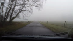 Vehicle shot in mist, narrow road in Dutch countryside Stock Footage