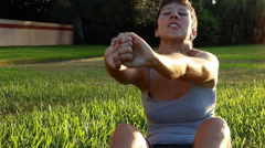 Woman stretching outdoors on grass Stock Footage