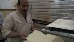 Fresh dough goes into oven, in Iranian bakery Stock Footage