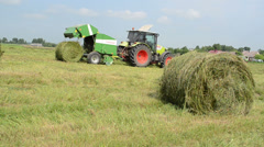 Closeup of hay bale and tractor baler discharge round fresh roll Stock Footage
