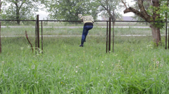 Hurry girl climb over fence and happy jump with smile in rain Stock Footage