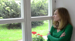 Sad shrinked woman sits on window sill and look far away. Stock Footage