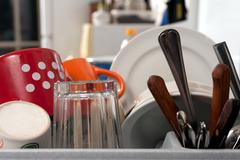 clean dishes, knives and forks and cups and plates - stock photo