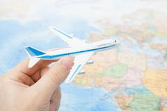 toy aircarft in hand with world map on background with focus on the plane - stock photo