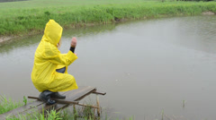 Woman with water proof coat on pond bridge feed fishes in rain Stock Footage