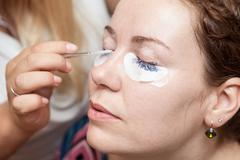 female eyelashes dyeing with permanent blue makeup - stock photo