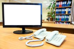 Monitor with isolated on white screen with telephones on desk in office Stock Photos