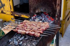 juicy slices of meat with sauce prepare on fire (shish kebab). - stock photo