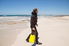 male diver with diving suit snorkel mask fins on the beach - stock photo