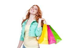 Smiling young redhead girl with colorful shoppingbags Stock Photos