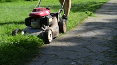 Gardener in shorts cut grass lawn with mower cutter stone path Stock Footage