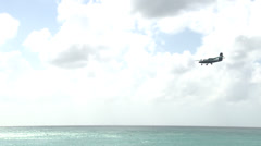 Medium Shot of a Plane Flying Above the Sea and Beach Stock Footage