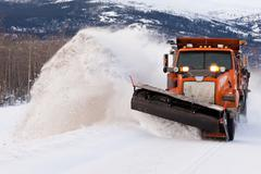 snow plough clearing road in winter storm blizzard - stock photo