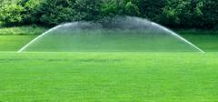 Two water sprinklers on lawn - stock photo