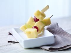 Skewered diced Emmentaler cheese with grapes on wooden table Stock Photos