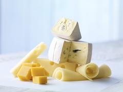Selection of Cheddar, blue cheese and Emmentaler cheese on wooden table - stock photo