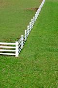 Corner of white fence on grass - stock photo