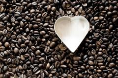 Stock Photo of Coffee beans arround heart-shaped cookie cutter