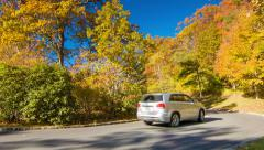 Vehicle Passing Fall Colored Trees in North Carolina Mountains Stock Footage