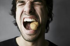 Stock Photo of Portrait of young man trying to crack a walnut with his teeth, studio shot