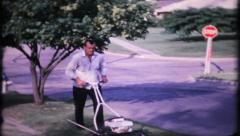 Home owner cuts his grass in the frontyard, 756 vintage film home movie  Stock Footage