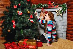 Girl sitting near christmas tree Stock Photos