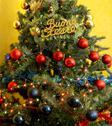 Stock Photo of decorated christmas tree with written happy holidays in italian