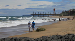 Couple walking on Umhlanga Rocks Beach Stock Footage