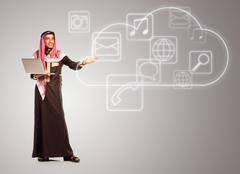 Young smiling arab with laptop shows virtual icons of the cloud service Stock Photos
