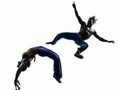 couple capoeira dancers dancing   silhouette - stock photo