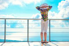 the girl admires air standing by chrome railing - stock photo